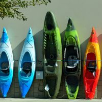 colorful kayaks displayed by the wall