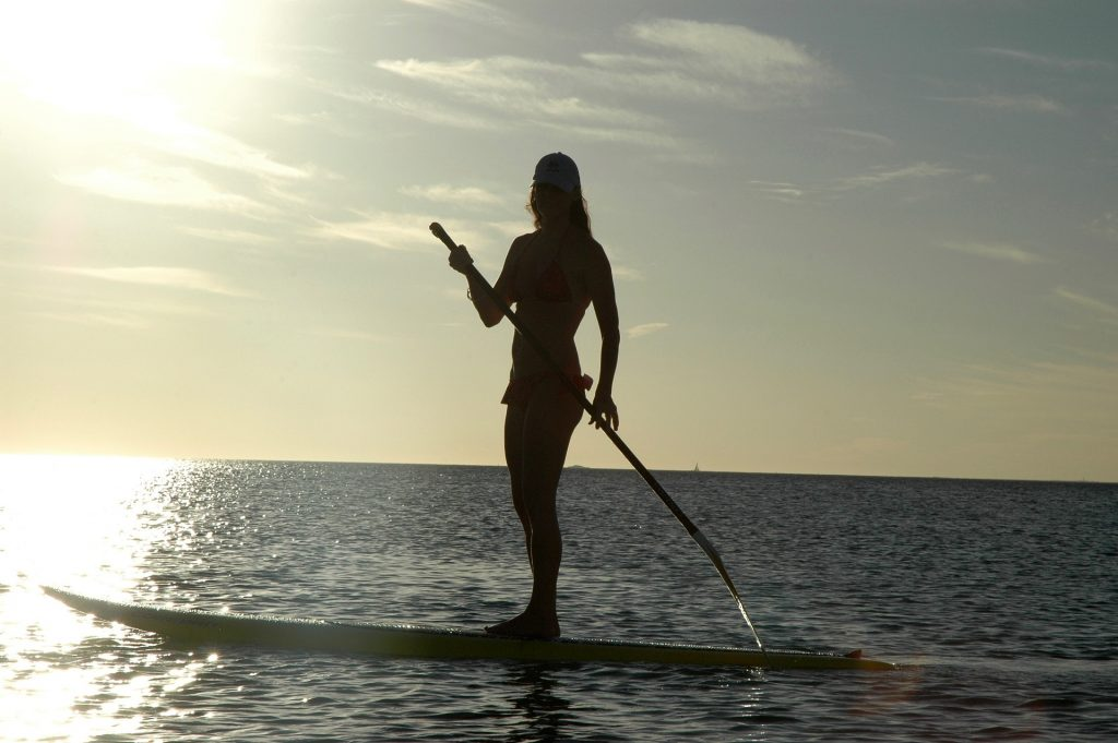 Woman on SUP with sunlight in the background