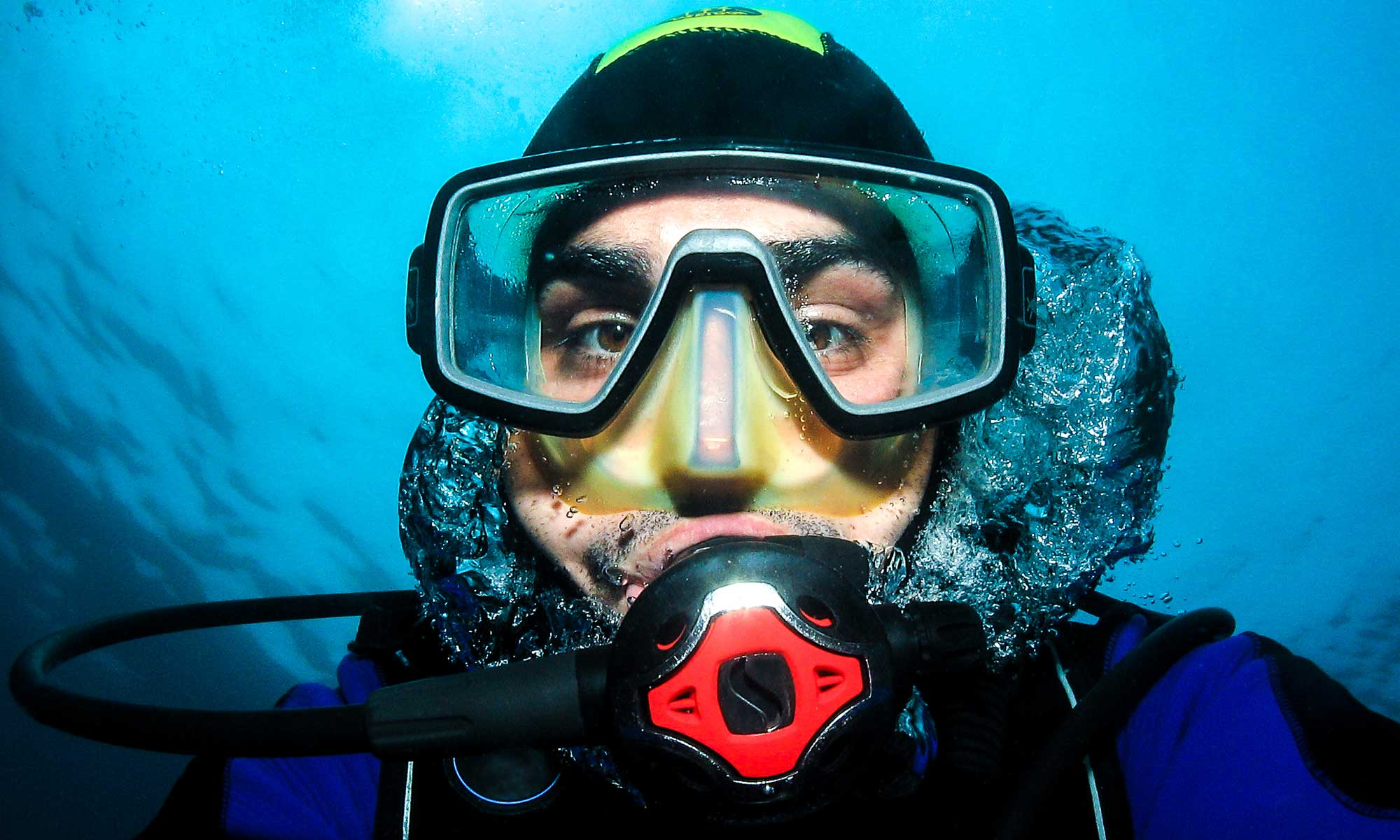 the diver takes a picture of his scuba mask