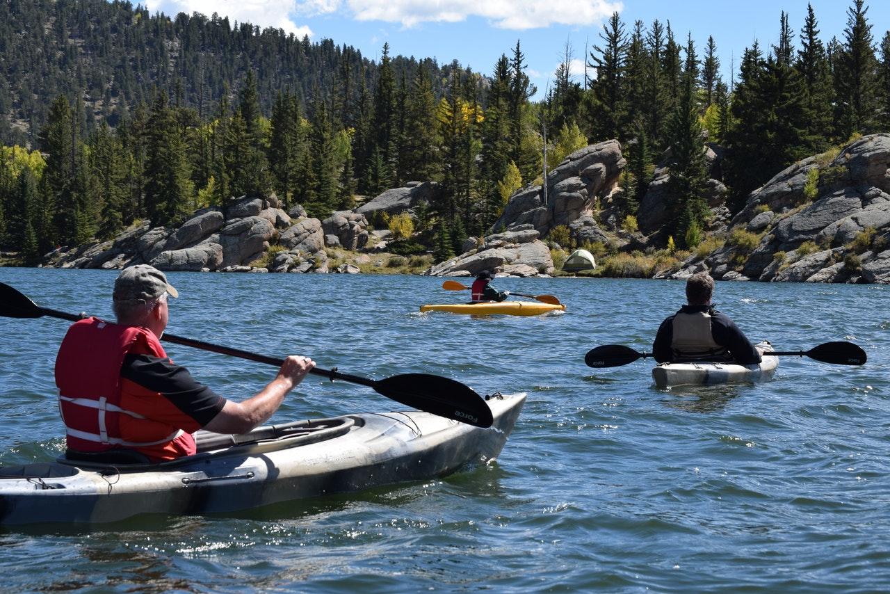 three men riding kayaks on a river