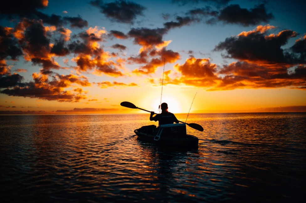 man in fishing kayak headed into the sunset