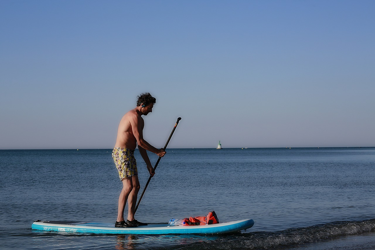 man standing on a surfboard wearing water shoes