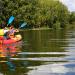woman enjoying the benefits of kayaking in a red kayak and white tanktop