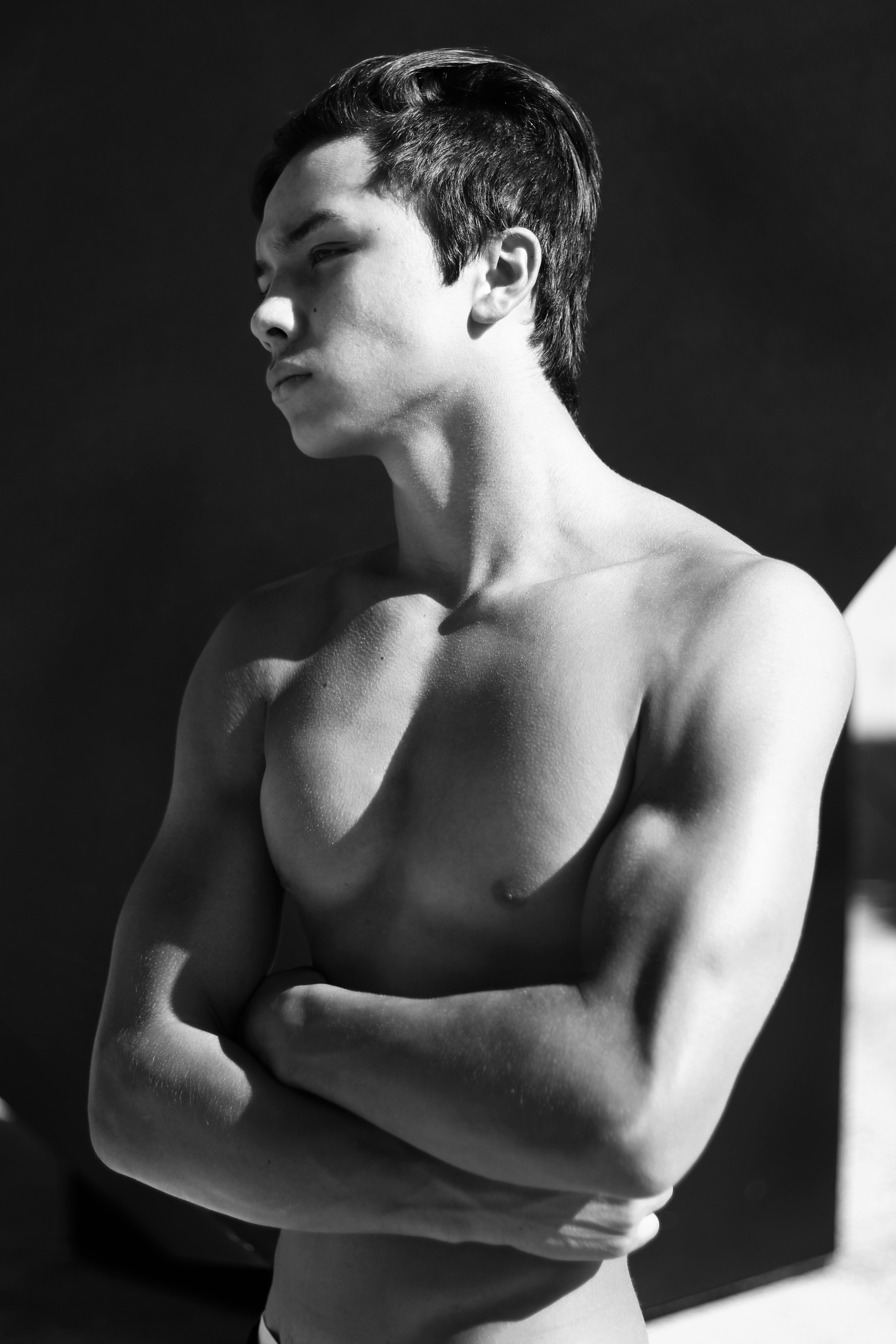 Black and white photo of a shirtless man showing his chest
