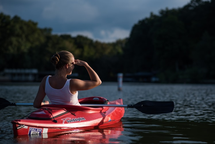 Woman paddling the kayak boat while covering her face from the sun light