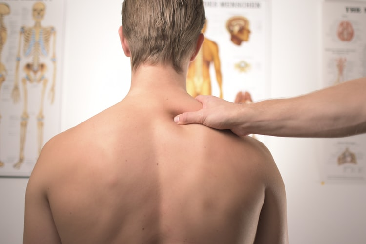 A person is massaging other person's shoulder