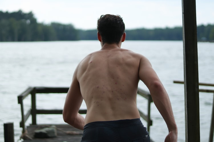 Man is going to the sea showing her back muscles