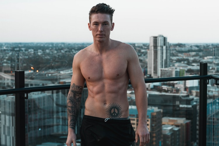 Photo of a Shirtless mas showcasing his abs with the city view as a background