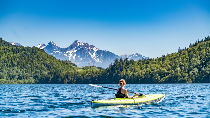 woman kayaking on lake during daytime