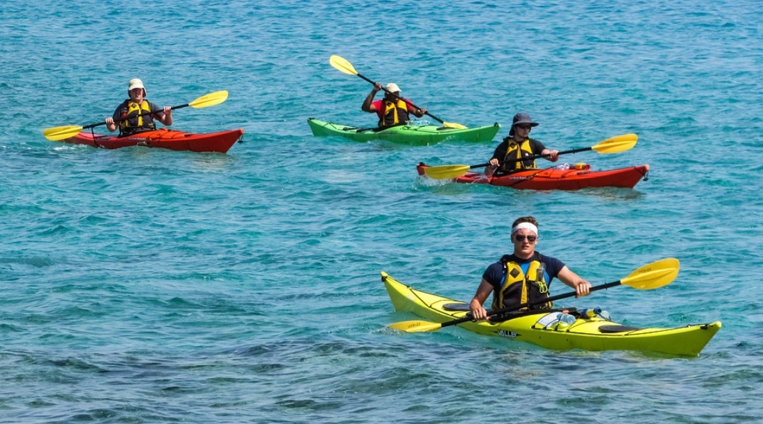 group of kayakers on the water in safety gear and vests, d
