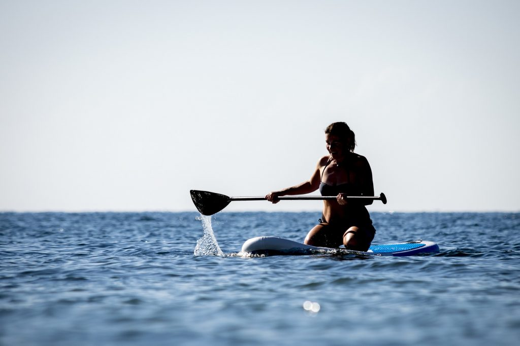 A woman kneeling on an iRocker paddleboard